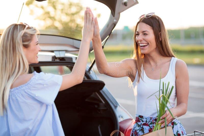 Två lyckliga unga kvinnor som ger sig hög-pickolaflöjter efter en rolig dag av shopping fotografering för bildbyråer