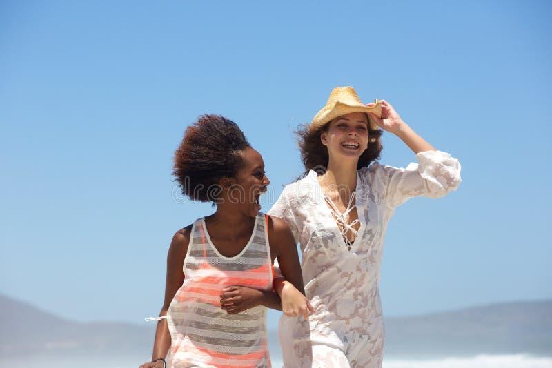 Två lyckliga unga kvinnor som tillsammans går på stranden arkivfoto