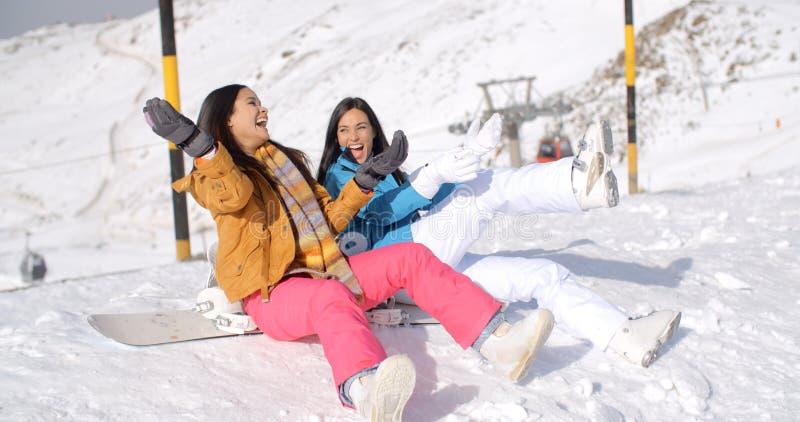 Två lyckliga unga kvinnor som tycker om en vinterferie arkivfoton