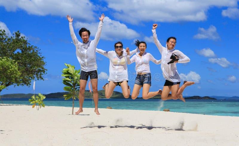 Två lyckliga unga par hoppar på den tropiska vita stranden arkivfoton