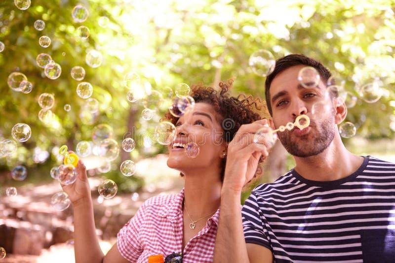 Två lyckliga unga vänner som blåser bubblor royaltyfria bilder