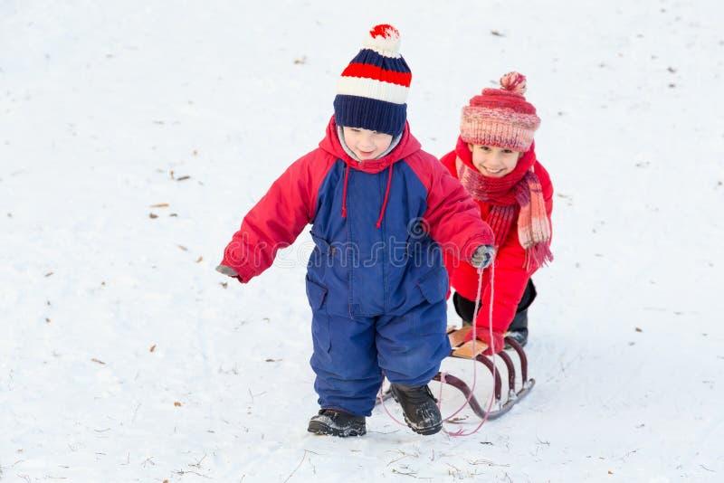 Två lyckliga ungar med släden som går på snö, sluttar royaltyfri foto