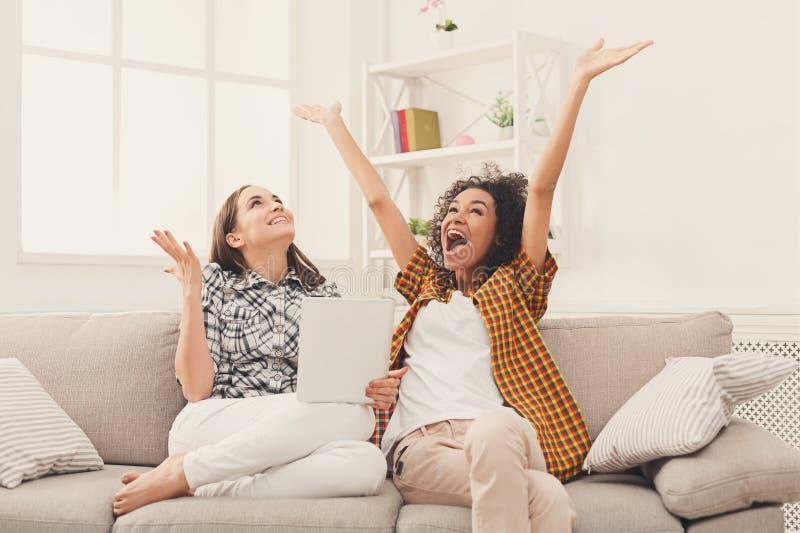 Två lyckliga upphetsade kvinnliga vänner som använder minnestavlan fotografering för bildbyråer