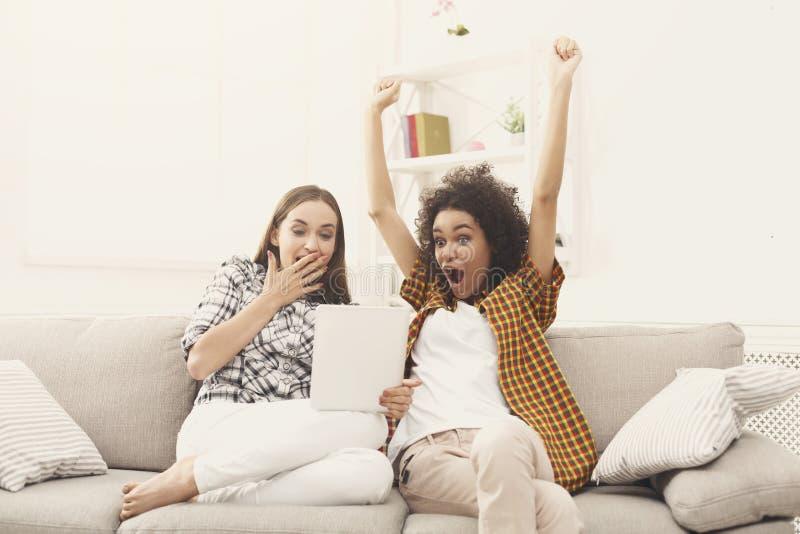 Två lyckliga upphetsade kvinnliga vänner som använder minnestavlan royaltyfri foto