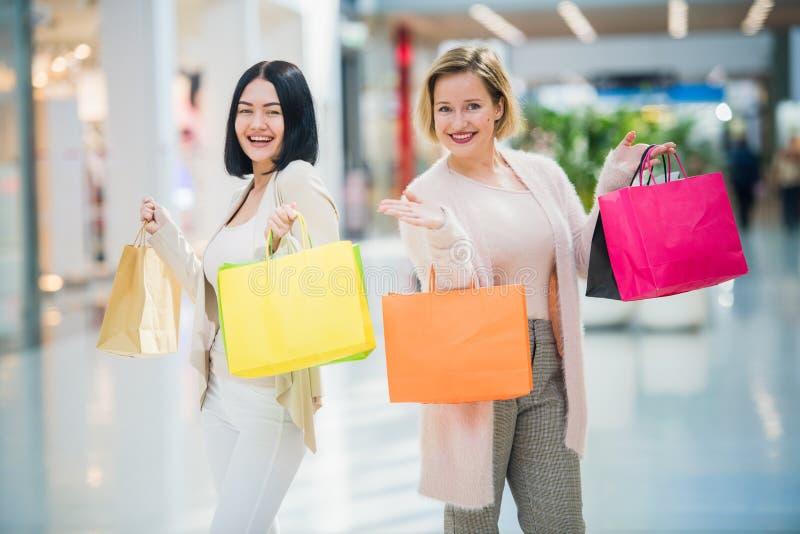 Två lyckliga vänflickor med shoppingpåsar som går i galleria royaltyfria bilder