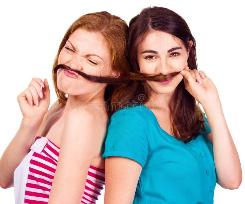 Två lyckliga vänner för unga kvinnor som spelar med hår som mustaschen royaltyfri bild