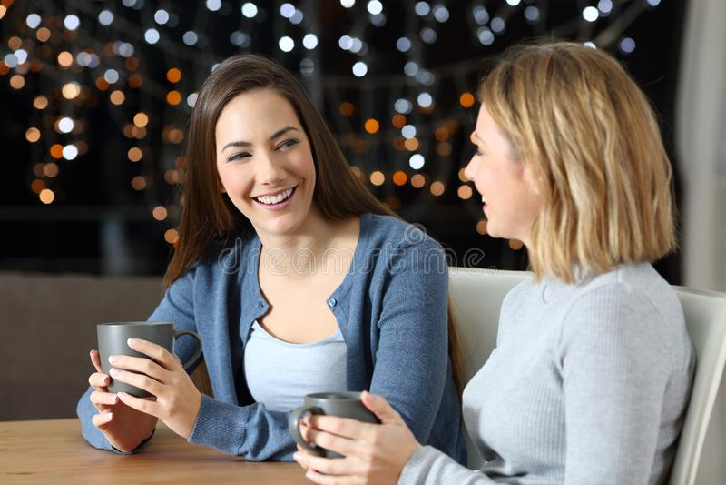 Två lyckliga vänner som hemma talar i natten arkivfoton