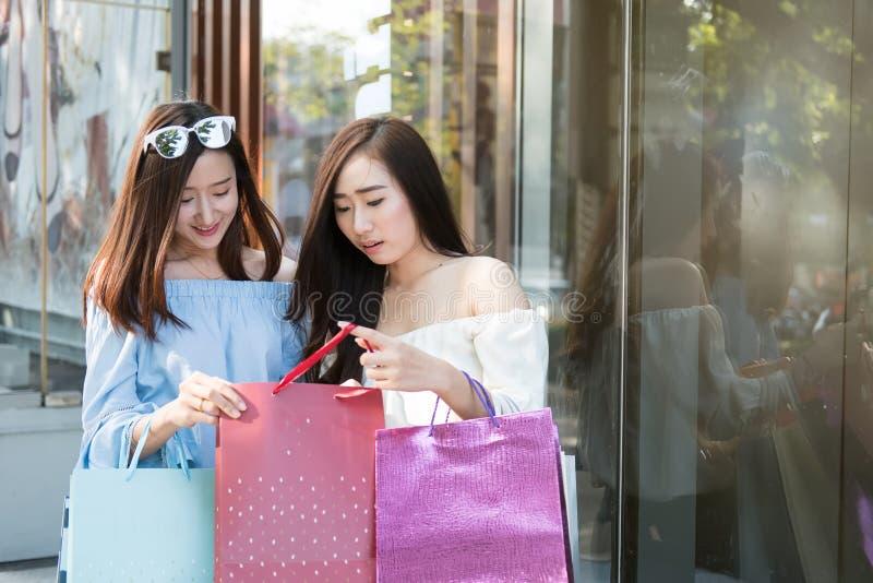 Två lyckliga vänner som shoppar i ferietid fotografering för bildbyråer