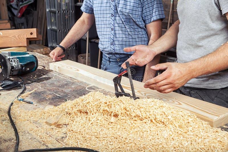 Två män diskuterar hur man bearbetar ett träbräde royaltyfria foton