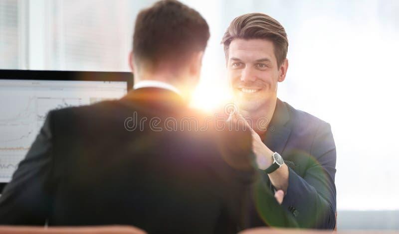 Två män diskuterar tillväxten av företaget som ser resningen royaltyfria foton