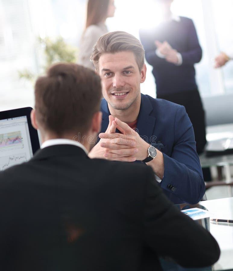 Två män diskuterar tillväxten av företaget som ser resninggrafen på en datorskärm arkivbild