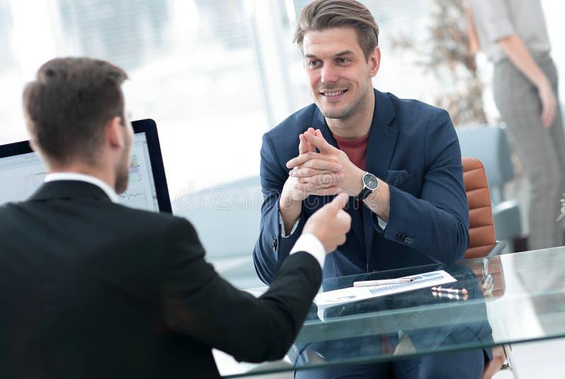 Två män diskuterar tillväxten av företaget som ser resninggrafen på en datorskärm royaltyfria foton