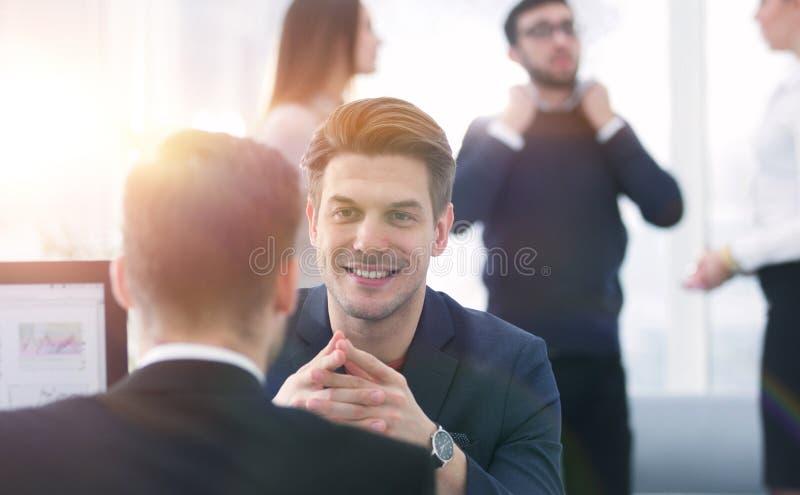 Två män diskuterar tillväxten av företaget som ser resninggrafen på en datorskärm royaltyfri fotografi