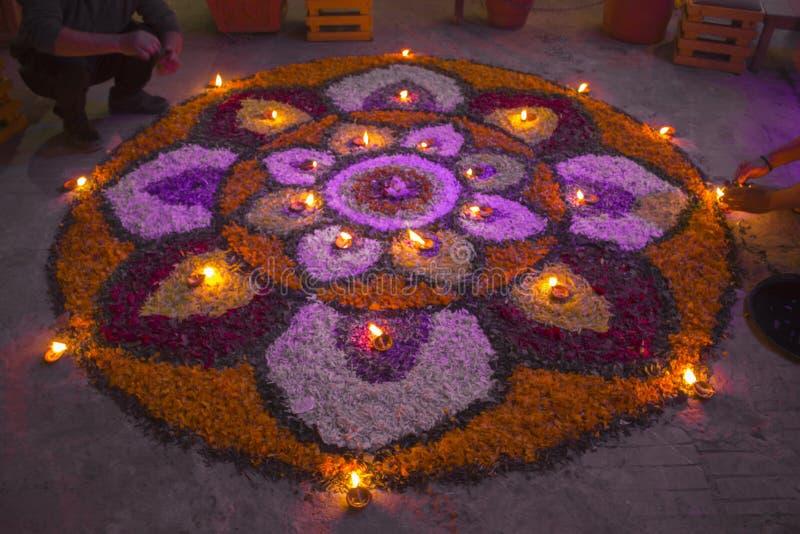 Två män gör en mandala av blommor med brinnande stearinljus i aftonen av festivalen av Diwali Rangoli arkivfoton