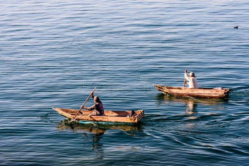 Två män i dugoutkanoter på sjön Atitlan, Guatemala arkivfoton