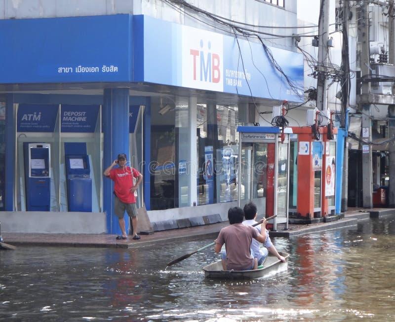 Två män i en eka förbigår en TMB-bank i en översvämmad gata i Rangsit, Thailand, i Oktober 2011 arkivbild