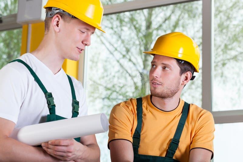 Två män i overaller och hardhat under arbete arkivbild