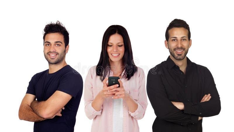 Två män i svart och en kvinna som ser mobilen royaltyfria bilder
