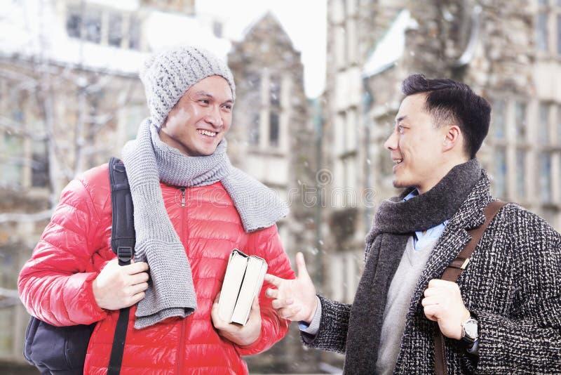 Två män, i vinterklädersamtal arkivbilder