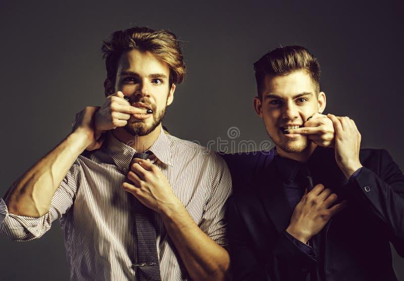 Två män med kvinnliga fingrar royaltyfri bild
