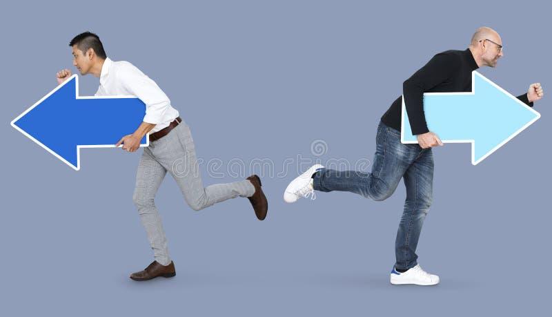 Två män med pilar och spring i motsatta riktningar royaltyfri fotografi