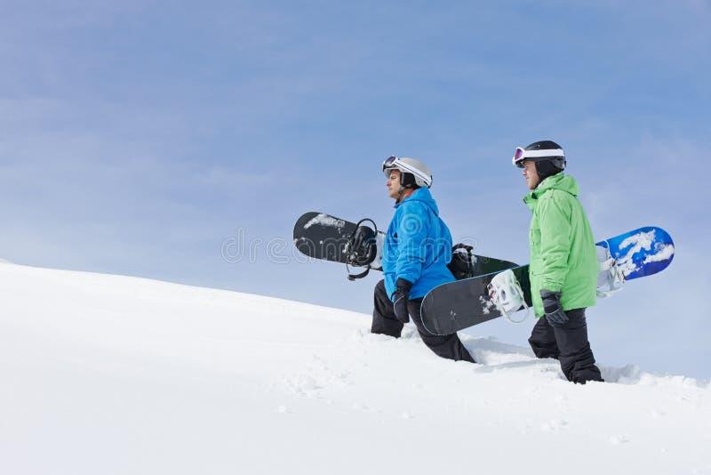 Två män med Snowboards på Ski Holiday In Mountains royaltyfri foto