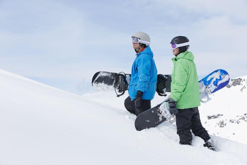 Två män med Snowboards på Ski Holiday In Mountains royaltyfri fotografi