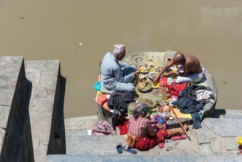 Två män och en kvinna som in äter på bankerna av den Bagmati floden royaltyfria foton