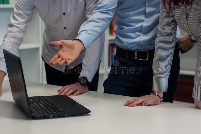 Två män och en kvinna som arbetar på ett företags projekt Man i bet royaltyfria bilder