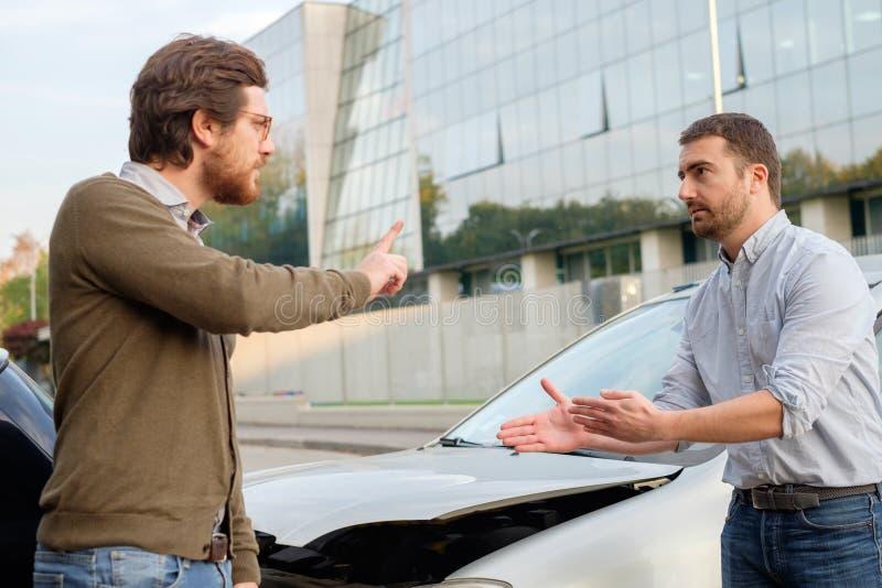 Två män som argumenterar efter en bilolycka på vägen arkivbild
