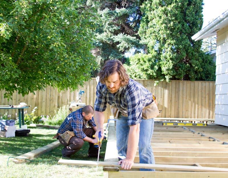 Två män som bygger ett däck arkivbild
