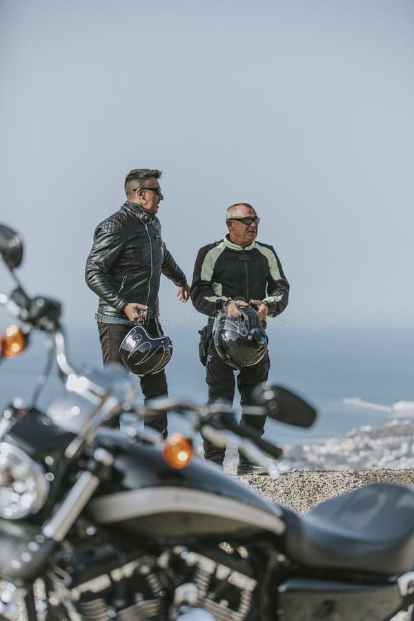 Två män som har ett avbrott efter mopedritt, med bakgrunden för hav och för blå himmel royaltyfri foto