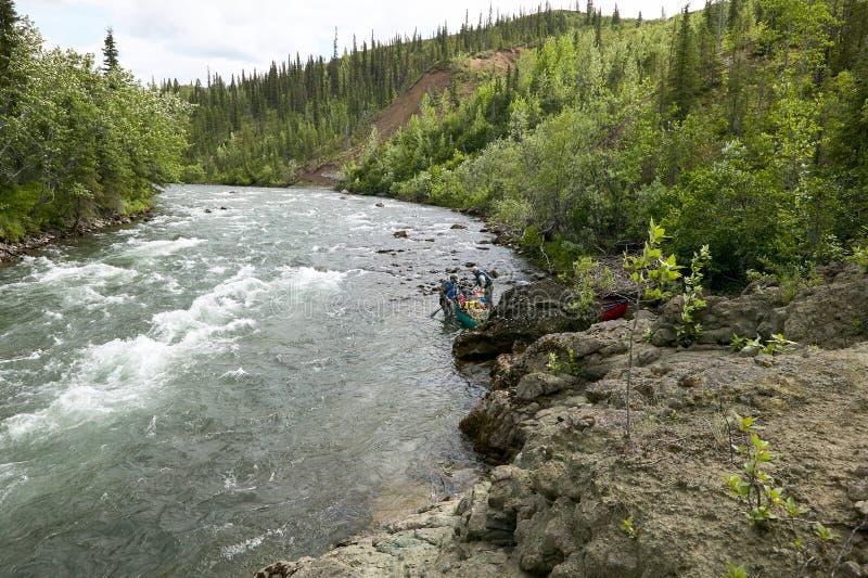 Två män som lanserar kanoten på den lösa alaskabo floden arkivfoto