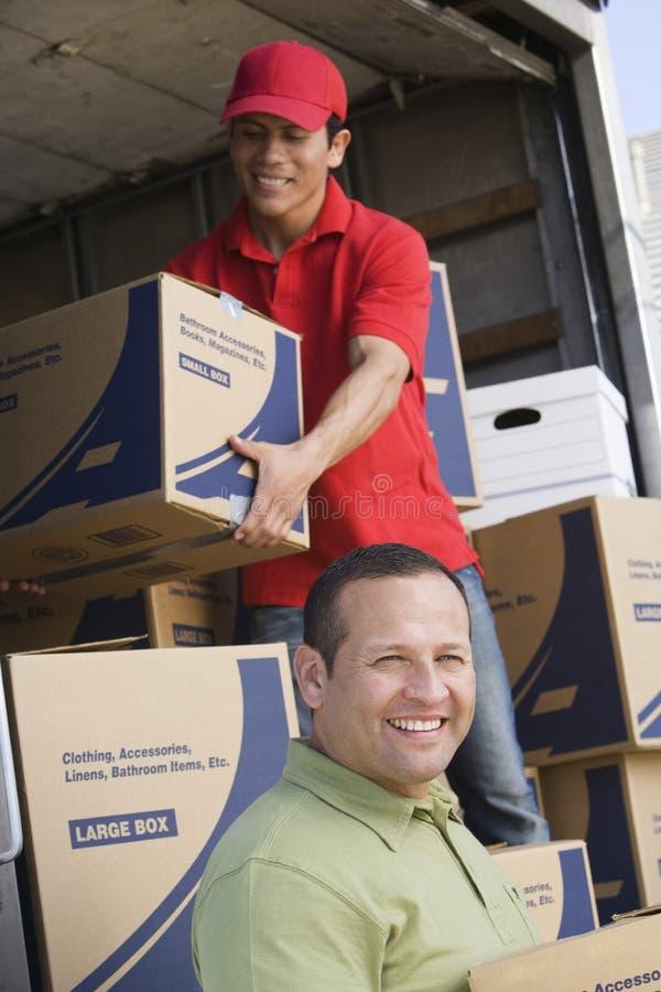 Två män som lastar av leveransskåpbilen arkivfoton