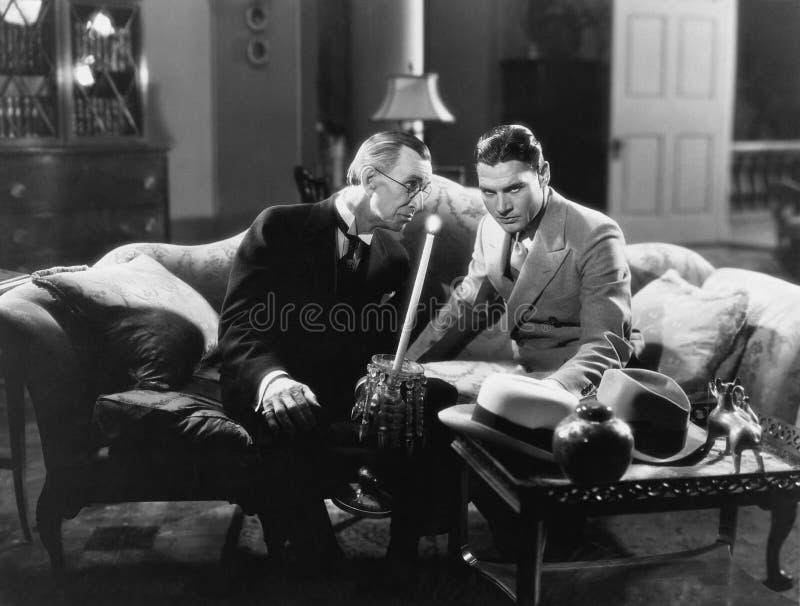 Två män som sitter på en soffa (alla visade personer inte är längre uppehälle, och inget gods finns Leverantörgarantier att det s fotografering för bildbyråer