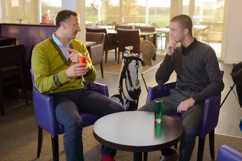 Två män som sitts i stången som har drinken arkivbild
