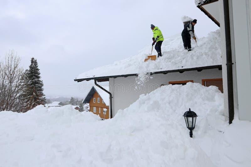 Två män som skyfflar hög tung snö från ett hustak arkivfoto