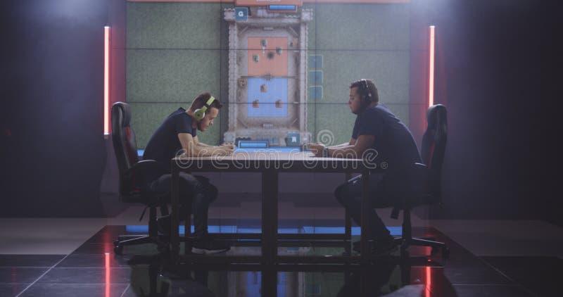 Två män som spelar den mobila leken på en turnering royaltyfria bilder