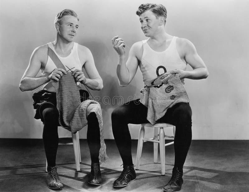 Två män som sticker och syr (alla visade personer inte är längre uppehälle, och inget gods finns Leverantörgarantier att det ska  arkivbilder