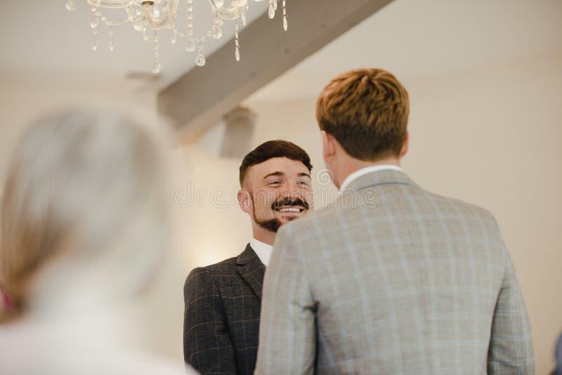 Två män som utbyter löften på deras bröllopdag arkivfoton