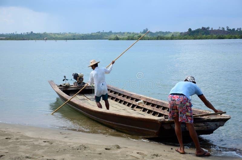 Två män sorterar färjan ut över floden arkivfoto