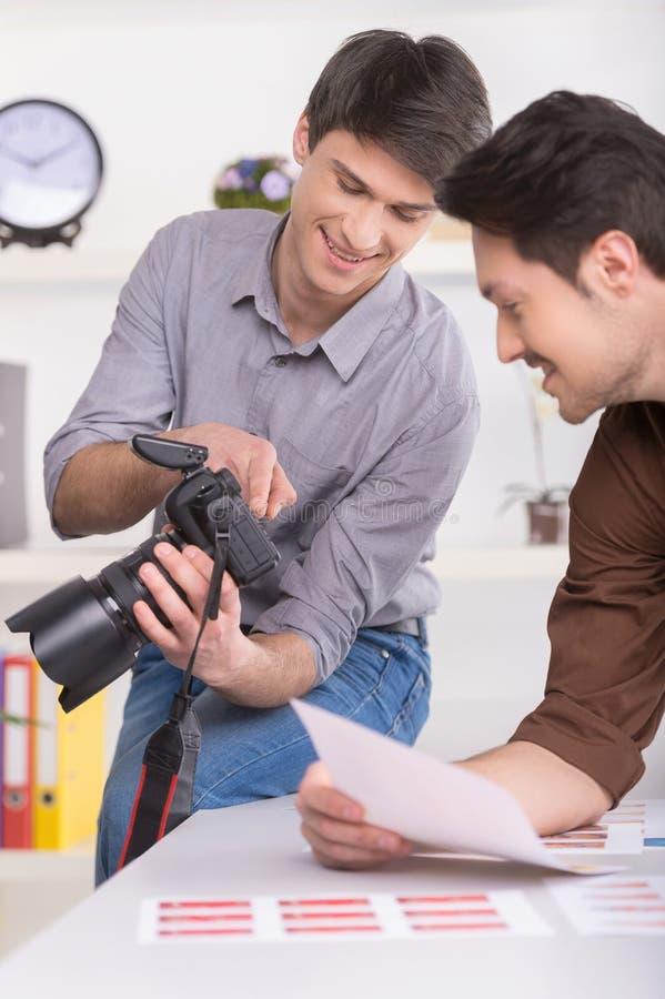 Två män väljer ett foto från en fors. arkivfoton