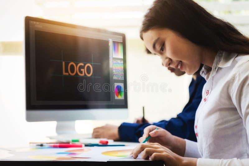 Två märkes- grafiska idérika personer som arbetar om websitedesign med datoren och vald färgstil för nytt projekt på kontoret arkivfoton