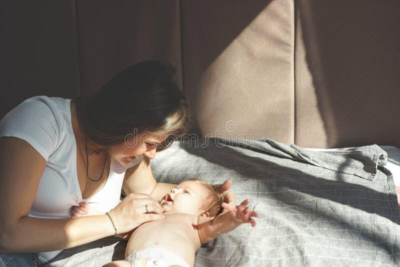 Två-månaden behandla som ett barn utan kläder, naket som ligger i en blöja och ler på modern royaltyfri fotografi