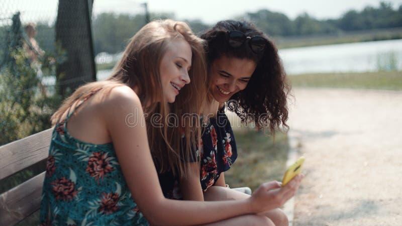 Två mång--person som tillhör en etnisk minoritet flickor som använder mobiltelefonen, medan sitta på en bänk arkivfoton