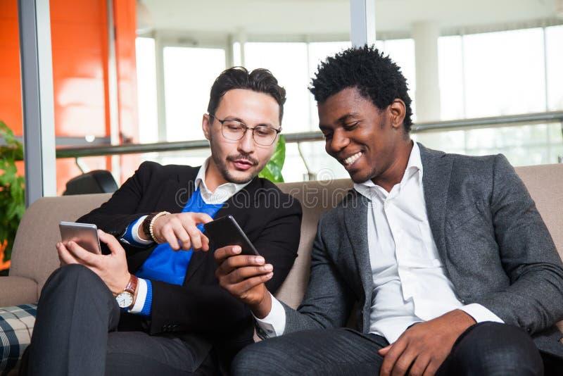 Två mångkulturella män sitter på soffa-, leende- och hållmobiltelefoner arkivbild