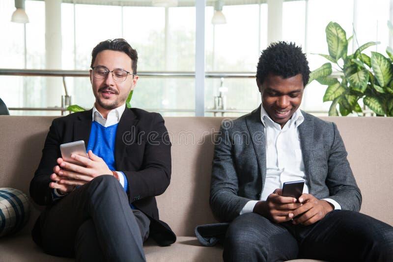 Två mångkulturella män sitter på soffan och rymmer mobiltelefoner fotografering för bildbyråer