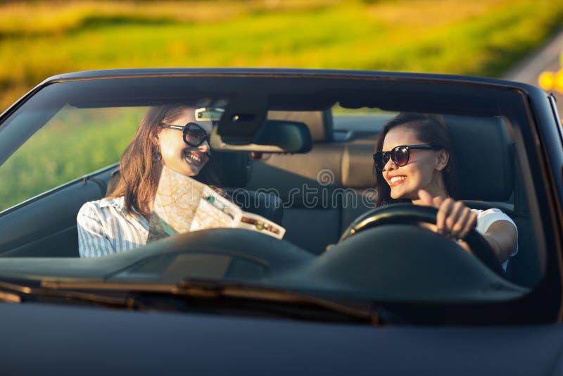 Två mörker-haired unga kvinnor i solglasögon sitter i en konvertibel bil och ler på en solig dag Ett av dem uppehällen royaltyfri fotografi
