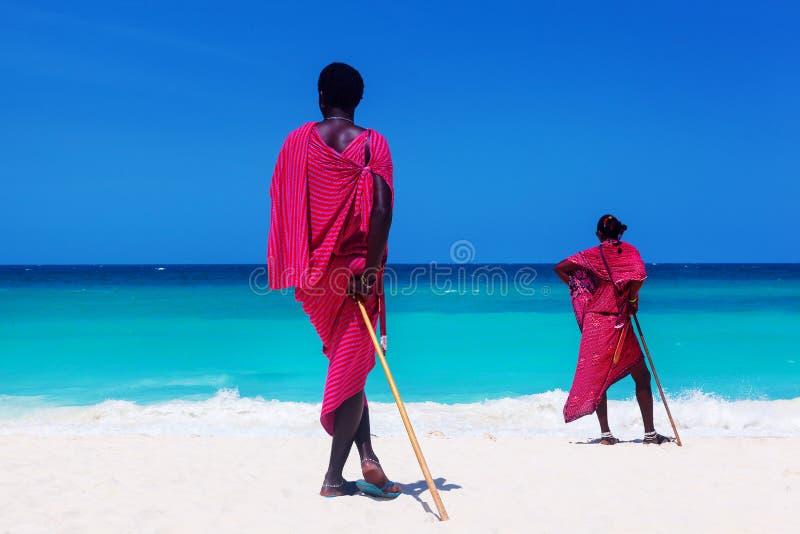 Två maasaikrigare som ser på havet fotografering för bildbyråer