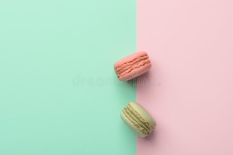 Två macarons jordgubbe och pistaschanstrykning på pastellfärgad grön chartreuse rosa bakgrund för duotone Konfekt för fransk bake royaltyfri bild